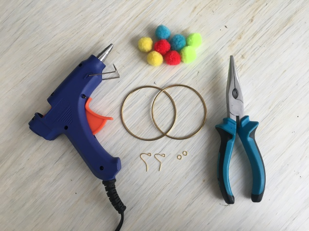 1. Gather the items - glue gun, pliers, two bangles, earring hooks, pom poms
