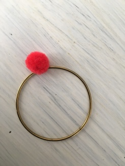 3. Attach the pom pom onto a bangle, repeat until desired