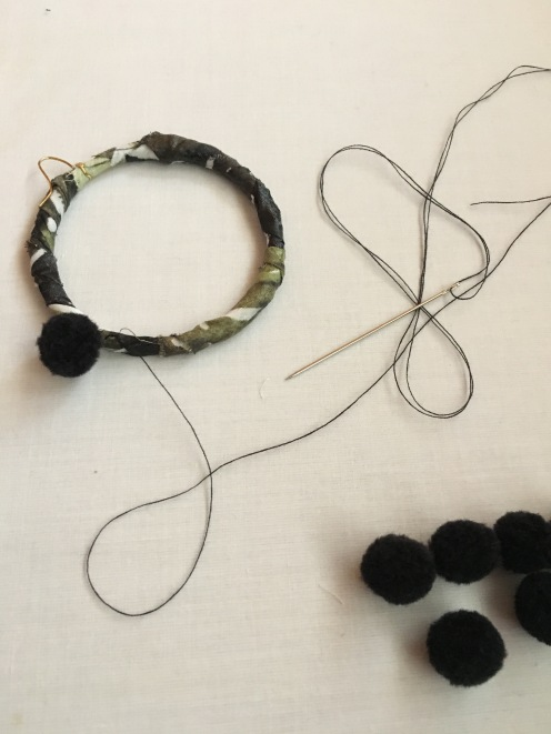 6. With a needle and thread, stitch ten pom poms around the hoop frame. Repeat on other hoop.