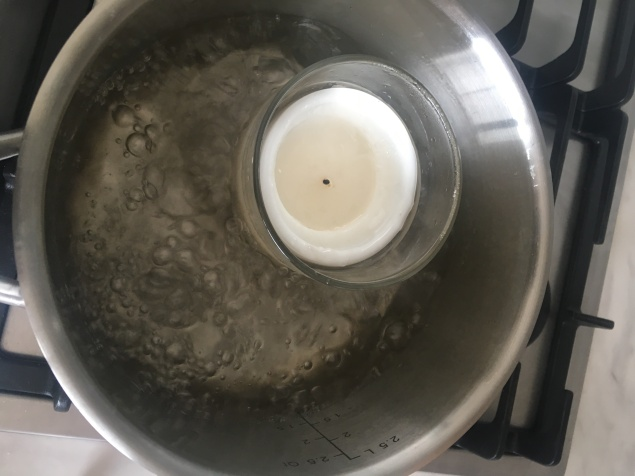 3. Add water to a pot and boil candle until wax melts.
