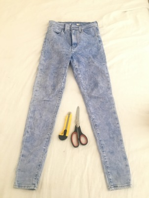 1. Lay the jeans on a flat surface. Have a pair or scissors and a blade in hand.